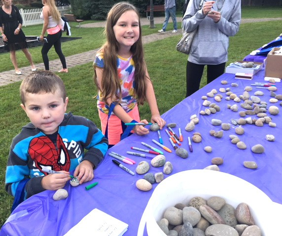 Top: Four-year-old Liam Brandon and his 9-year-old sister, Natalia, write messages on rocks that were placed in the garden in memory of their dad who passed away as the result of a drug overdose. Above: The ribbon is cut by Supervisor Ken Schmitt and vigil organizer Lauren Privitera which formally opens the garden. Photos by Eric Gross