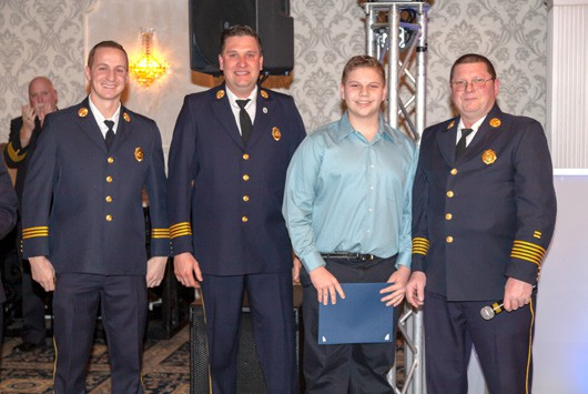 Future Putnam firefighter Joseph Nikisher is heralded as a hero by his dad, Mahopac FD Chief Bill Nikisher and his assistant chiefs Andrew Roberto and Jason Kinash. Photo By Tom Bea ty