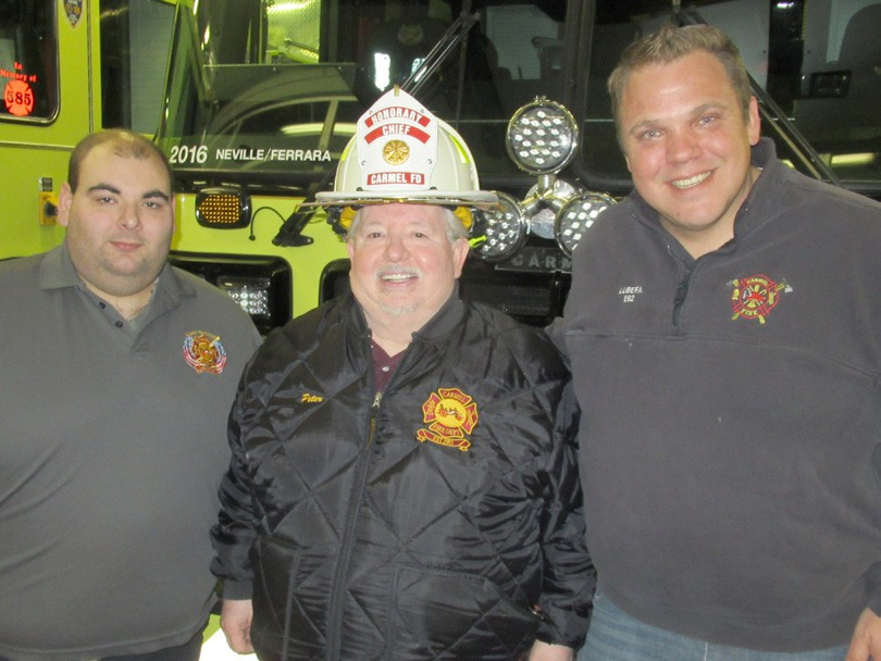 Peter Madden is congratulated by Carmel Assistant Chiefs Matt Lubera (right) and Scott Efferen on his honorary chief recognition last week at CFD headquarters. Photo By Eric Gross