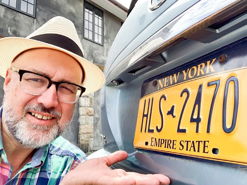 Doug Cunningham takes a selfie with his perfectly good NY State license plate and 14-year-old serviceable sedan.