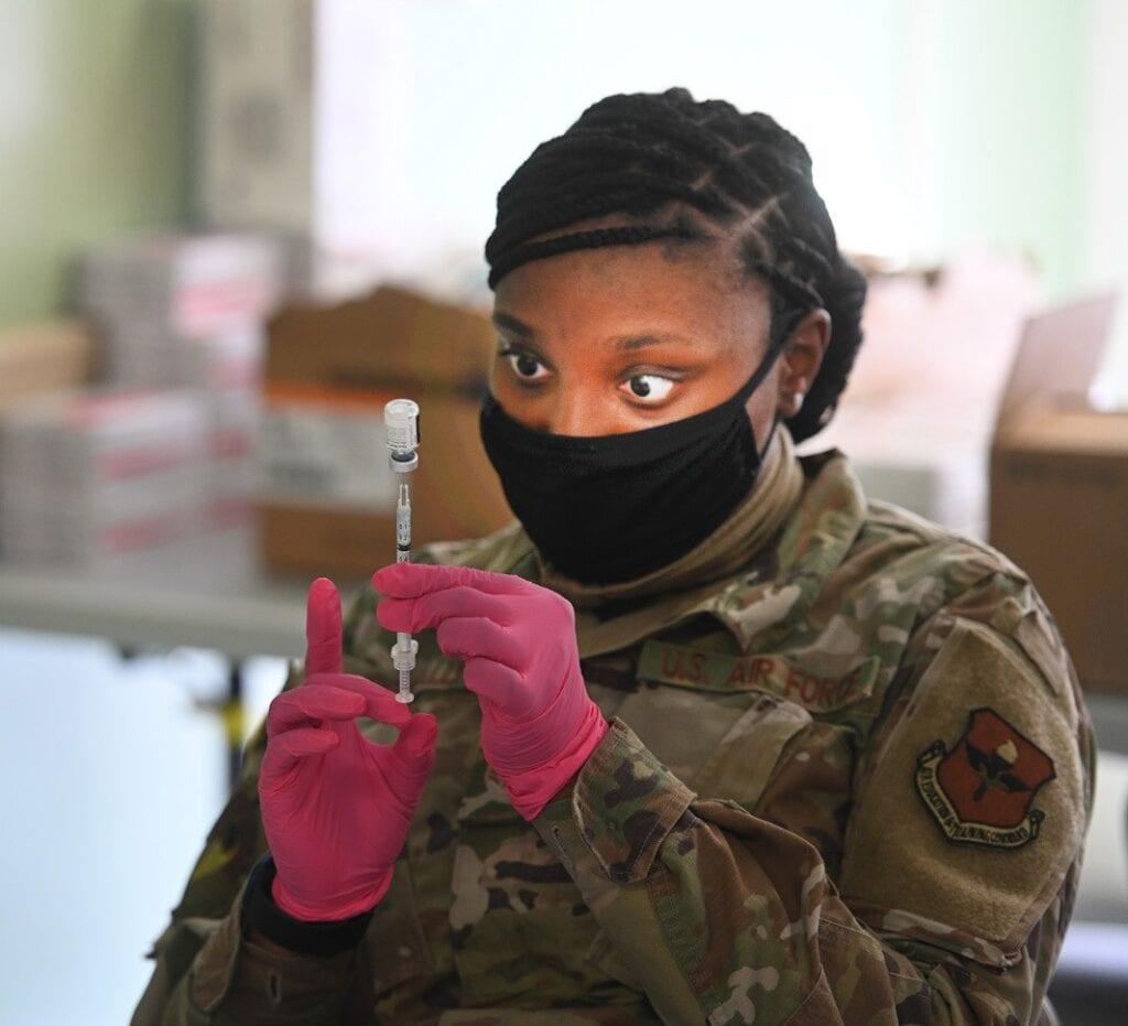Photos: Bottom, Governor Cuomo announces opening of joint State-FEMA Mass Vaccination Sites at York College in Queens and Medgar Evers College in Brooklyn last Wednesday, Feb. 24. The overall shot is of the State-FEMA mass vaccination site at York College. (Photo Don Pollard// Office of the Governor). The other photograph depicts a medical member of the National Guard preparing Pfizer Covid-19 vaccines at Medgar Evers College. (Kevin P. Coughlin / Office of Governor Andrew M. Cuomo)