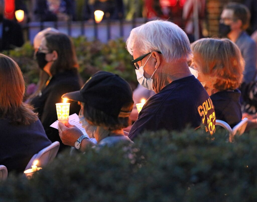 The audience of family members, friends and others lit candles as the names of those lost on 9/11 and since then from related causes were read. Photo by Douglas Cunningham.